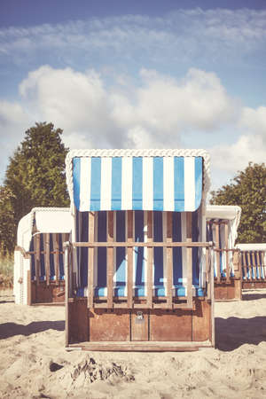 Retro toned picture of an empty wicker beach chair on sand. Standard-Bild