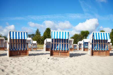 Empty wicker beach chairs on sand.