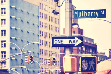 New York City street signs and traffic lights by Mulberry Street, once the heart of Manhattan Little Italy, Color toned picture, USA.