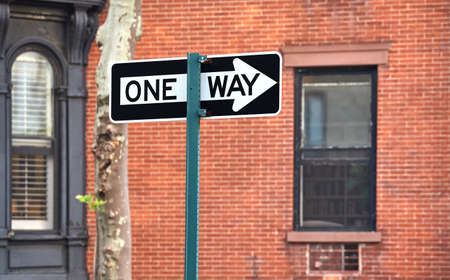 One way street sign with old building in background, selective focus, New York, USA.