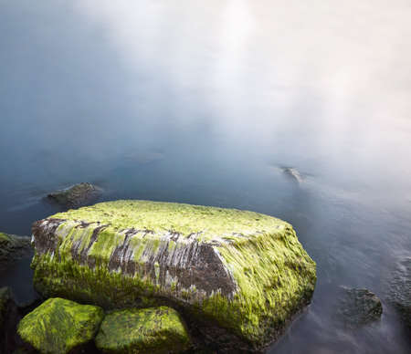 Rocks covered with green algae in water, long exposure picture.