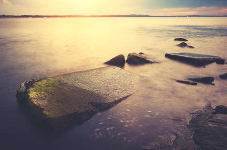 Rocks in water at sunset, color toning applied, Swinoujscie, Poland. Standard-Bild
