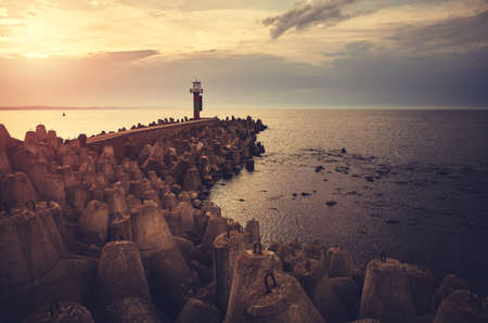 Pier with lighthouse protected by breakwater tetrapods at sunset, color toning applied.