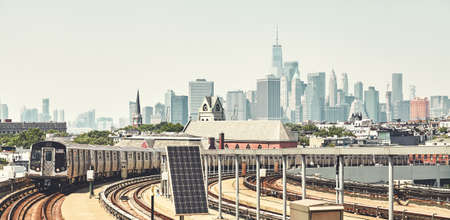 New York subway train with Manhattan skyline in background, color toned picture, USA.