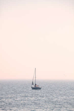 Sailing sailboat on a foggy day, color toning applied. Standard-Bild