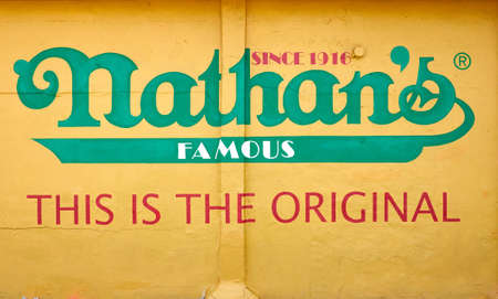 New York, USA - July 02, 2018: The Nathan's Famous sign painted on wall of restaurant specializing in hot dogs on Coney Island. Editorial