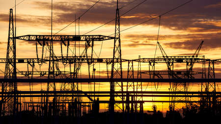 Power plant transmission infrastructure silhouette at sunset.