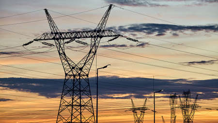Power transmission towers silhouettes at sunset. Standard-Bild