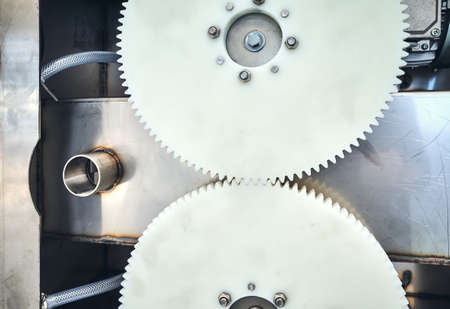 Close up of two plastic meshing gears transmitting rotational motion of a machine.