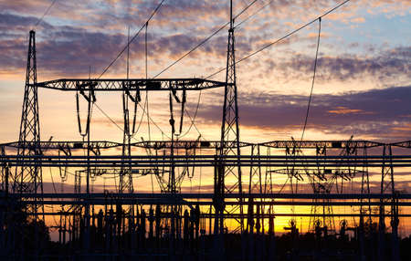 Power plant transmission infrastructure silhouette at purple sunset.