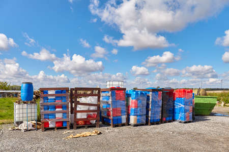 Chemicals in plastic containers at a dump site.