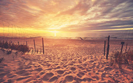 Scenic beach entrance at a beautiful sunset, color toned picture. Standard-Bild