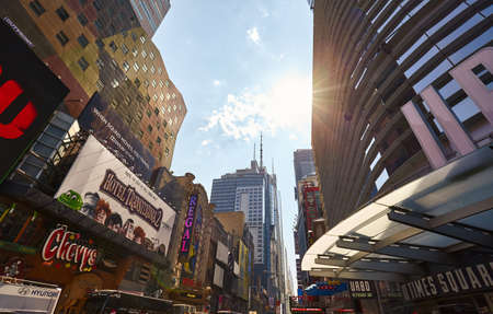 New York, USA - August 15, 2015: Manhattan with colorful ads on buildings against the sun.