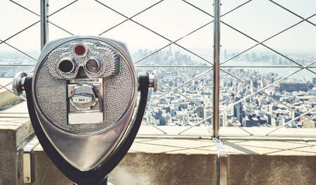 Coin operated binoculars with Manhattan skyline in background, retro color toning applied, New York City, USA.