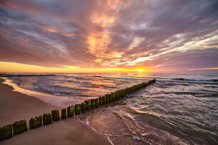Scenic sunset over Baltic Sea with an old wooden breakwater on the beach.