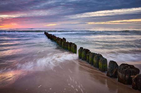 Old wooden breakwater at purple sunset, Baltic Sea coast, Poland.