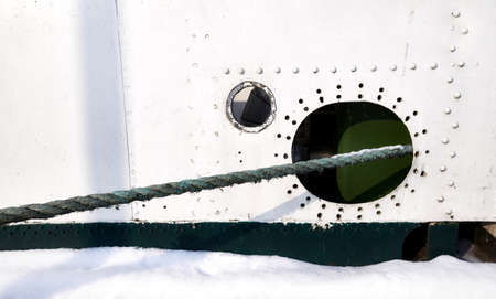 Old ship side with hole and hawser, nautical background.