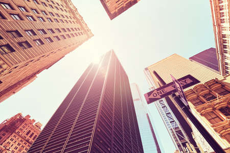 Looking up at Manhattan skyscrapers against the sun, color toned picture, New York City, USA. Stock Photo