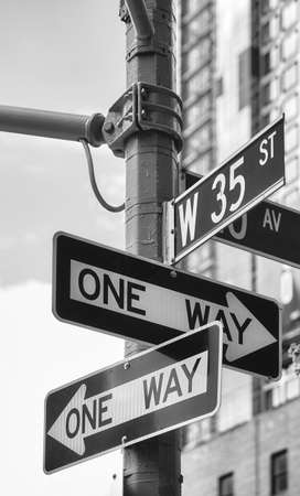 Black and white picture of One Way road signs at West 35th Street in New York City, USA.