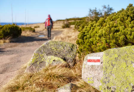 Red hiking trail marker painted on a rock, selective focus, Karkonosze National Park, Poland.