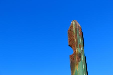 Rusty pole against blue sky
