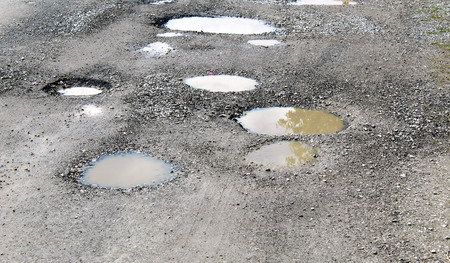 Potholes filled by water on a rural unpaved road