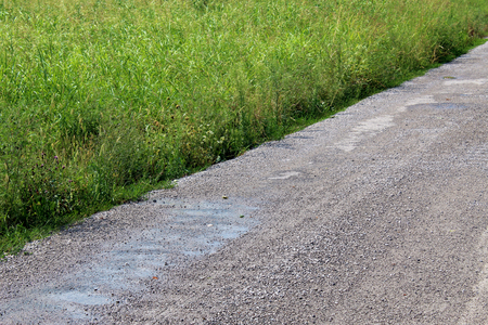 Detail of an unpaved rural road in the countryside close to a field