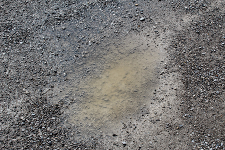 Small pothole full of water in a rural unpaved road