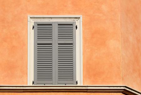 Closed shutter window on an orange wall