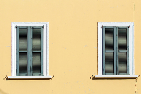 Closed shutter windows on a yellow building