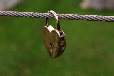 Gold heart shaped padlock hung on a metal wire with green background Stock Photo