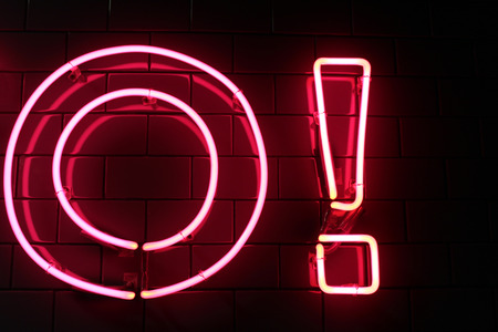 Red neon light letter and exclamation point (mark) on a black wall