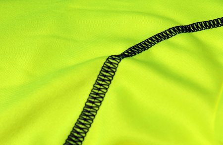 Black seam on a light green textile with folds (background focus)