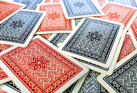 Texture of red and blue playing cards back spread on a table
