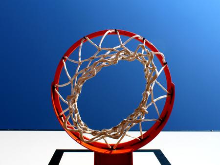 Basketball rim (hoop) seen from below against clear blue sky