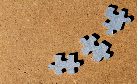 Three isolated puzzle game pieces on brown background Stockfoto
