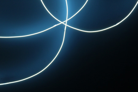Intertwined blue neon ccurved light on dark background