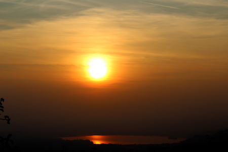 Sunset in an hazy sky and sun reflection in a small lake Stockfoto