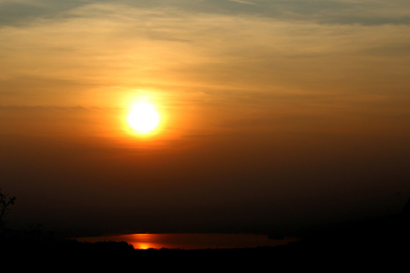 Sunset in a foggy sky with sun reflection on a small lake view from monte Barro (Italy) Stockfoto