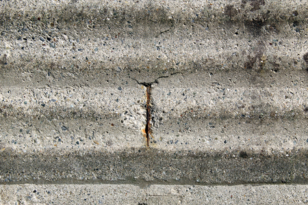 Rusty iron reinforcing bar (rod) emerging from an old concrete wall