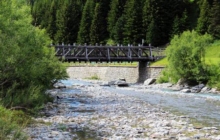 Side view of a wooden pedestrian bridge crossing a mountain creek Stockfoto