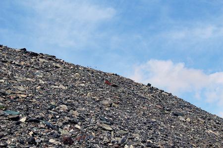Grey metamorphic rocks debris against blue sky