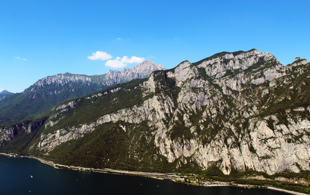 Vertical mountain side covered by trees over a lake in summer
