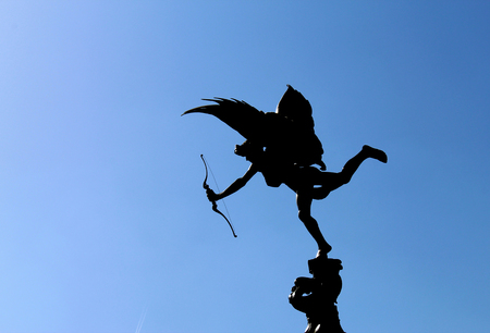 LONDON, UK - AUGUST 2018: Eros statue with bow and arrow against blue sky in Piccadilly Circus
