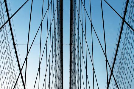 Metal bridge wires tie rods against blue sky