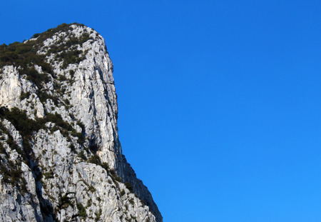 Vertical mountain cliff against clear blue sky in summer