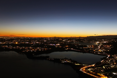 Sunset panorama over northern Lombardy lakes showing light pollution and Alps sihouette in the far background; Stockfoto