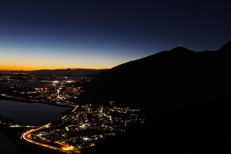 Night panorama from the Alps over northern Lombardy with city lights pollution and mountains silhouette