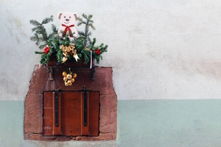 Old closed wooden small window with christmas decorations (pine tree and puppy)