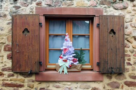 Shutter window with cut out clovers and christmas decorations (white small tree) on the windowsill